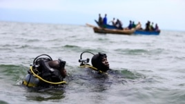 Members of the Uganda Police Marine Unit participate in rescue efforts after a boat carrying mostly Congolese refugees capsized in Lake Albert southwest of Uganda's capital, Kampala, March 23, 2014.
