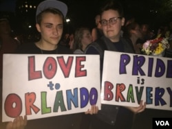 Attendees at the vigil hold signs in support of the victims of the Orlando attack. (K. Gypson/VOA)