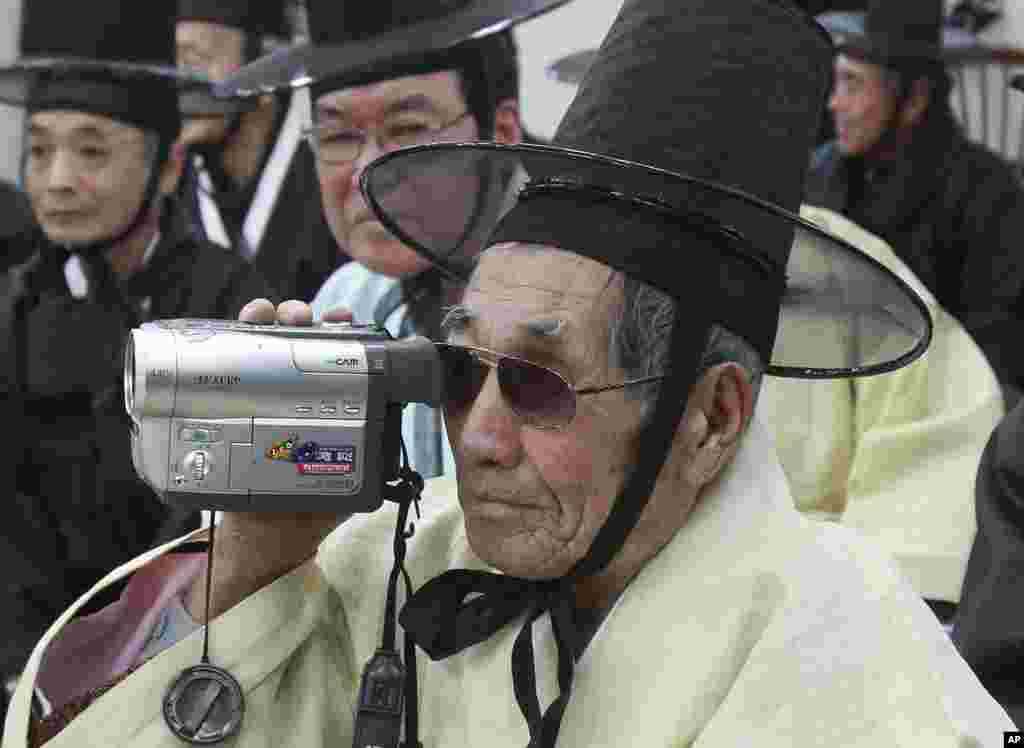 Village headman Jo Kyu-sang, 92, takes video during Lunar New Year celebration at Gangneung, South Korea.