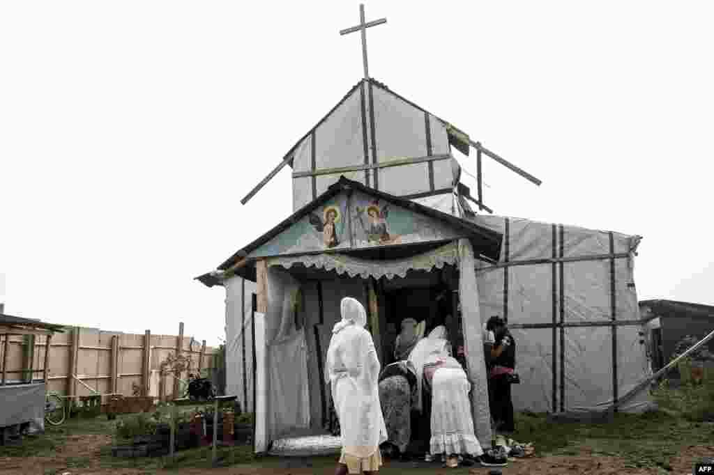 """Migran Kristen Koptik Ethiopia tiba untuk melakukan misa di gereja Orthodox darurat di kamp """"Jungle"""" di kota Calais, Perancis utara."""