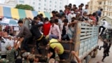 FILE: Cambodian migrant workers get off from a Thai truck upon their arrival from Thailand at a Cambodia-Thai international border gate in Poipet, Cambodia, Tuesday, June 17, 2014. (AP Photo/Heng Sinith)