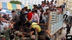 Cambodian migrant workers get off from a Thai truck upon their arrival from Thailand at a Cambodia-Thai international border gate in Poipet, Cambodia, Tuesday, June 17, 2014. The number of Cambodians who have returned home from Thailand this month after a threatened crackdown on foreigners working illegally has topped 160,000, a Cambodian official said Monday. Thai officials insist the cross-border movement is voluntary and is not forced repatriation. They say Thai military and government resources were used to transport workers who decided to return home after being laid off because they were working illegally. (AP Photo/Heng Sinith)