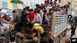 Cambodian migrant workers get off from a Thai truck upon their arrival from Thailand at a Cambodia-Thai international border gate in Poipet, Cambodia, Tuesday, June 17, 2014.