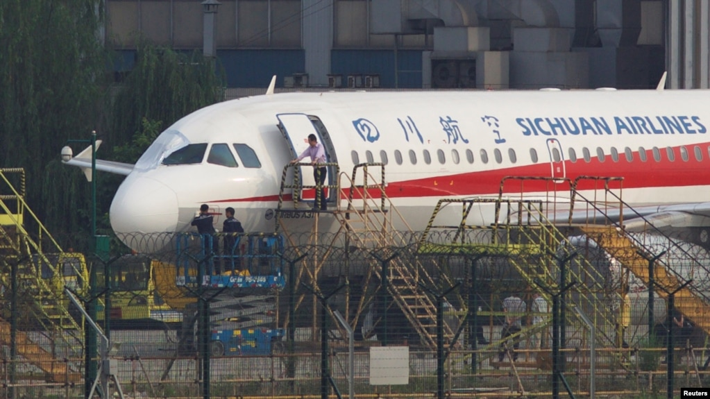 Workers inspect a Sichuan Airlines aircraft that made an emergency landing after a windshield on the cockpit broke off, at an airport in Chengdu, Sichuan province, China May 14, 2018. Picture taken May 14, 2018. REUTERS/Stringer