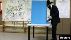 An ultra-Orthodox Jewish man stands near a booth at a polling station in the West Bank Jewish settlement of Kochav Ya'acov, north of Jerusalem, January 22, 2013.