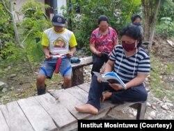 Sekelompok warga sedang membaca booklet Informasi Virus Corona yang disebarluaskan oleh posko informasi COVID-19 di Desa Trimulya, Poso Pesisir Utara, 2 April 2020. (Foto: Institut Mosintuwu)