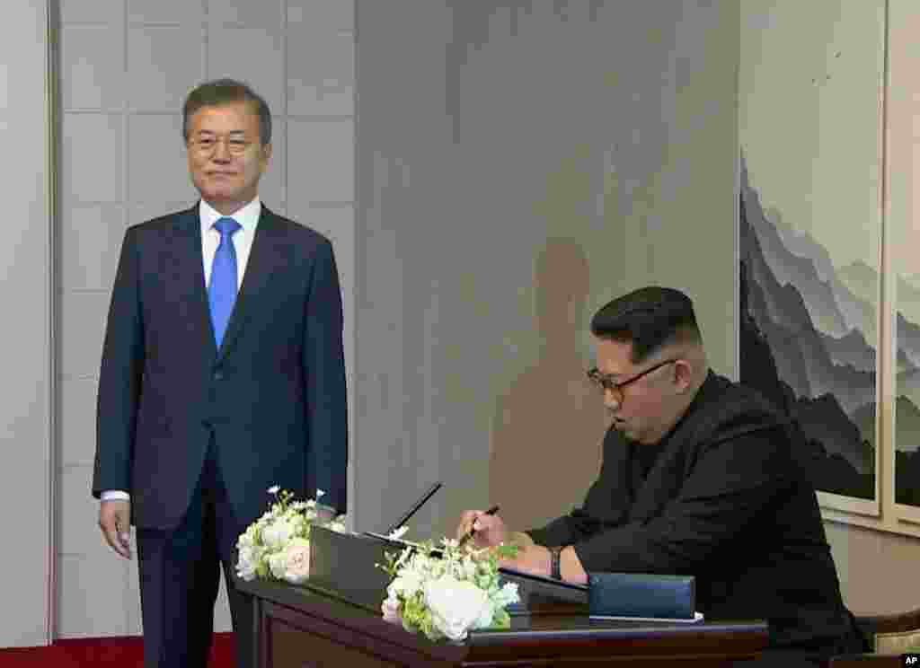 In this image made from video provided by Korea Broadcasting System (KBS), North Korean leader Kim Jong Un signs a guest book watched by South Korean President Moon Jae-in, left, inside the Peace House at the border village of Panmunjom in the Demilitariz