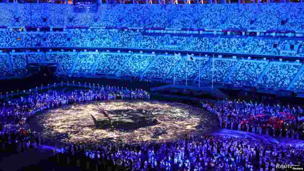 The Olympic Stadium is lighted up as athletes take part in the athletes' parade during the closing ceremony, Aug. 8, 2021.