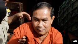 FILE-In this Sept. 21, 2016, photo, Cambodia's opposition lawmaker Um Sam An is escorted by prison security guards upon his arrival at Supreme Court in Phnom Penh, Cambodia. A Cambodian court on Monday, Oct. 10 sentenced Um Sam An who has been a strong critic of the government's handling of demarcating the border with neighboring Vietnam to 2 1/2 years in prison over online postings he made. (AP Photo/Heng Sinith)