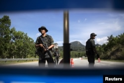 FILE - Members of the General Operations Force control the checkpoint on the road near the area where the abandoned human trafficking camp was discovered in the jungle close to the Thailand border at Bukit Wang Burma in northern Malaysia May 28, 2015.