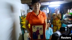 Than Dar, the wife of slain journalist Par Gyi, holds a family photograph showing herself, her husband and daughter posing with Aung San Suu Kyi at their home, in Yangon Oct. 28, 2014.