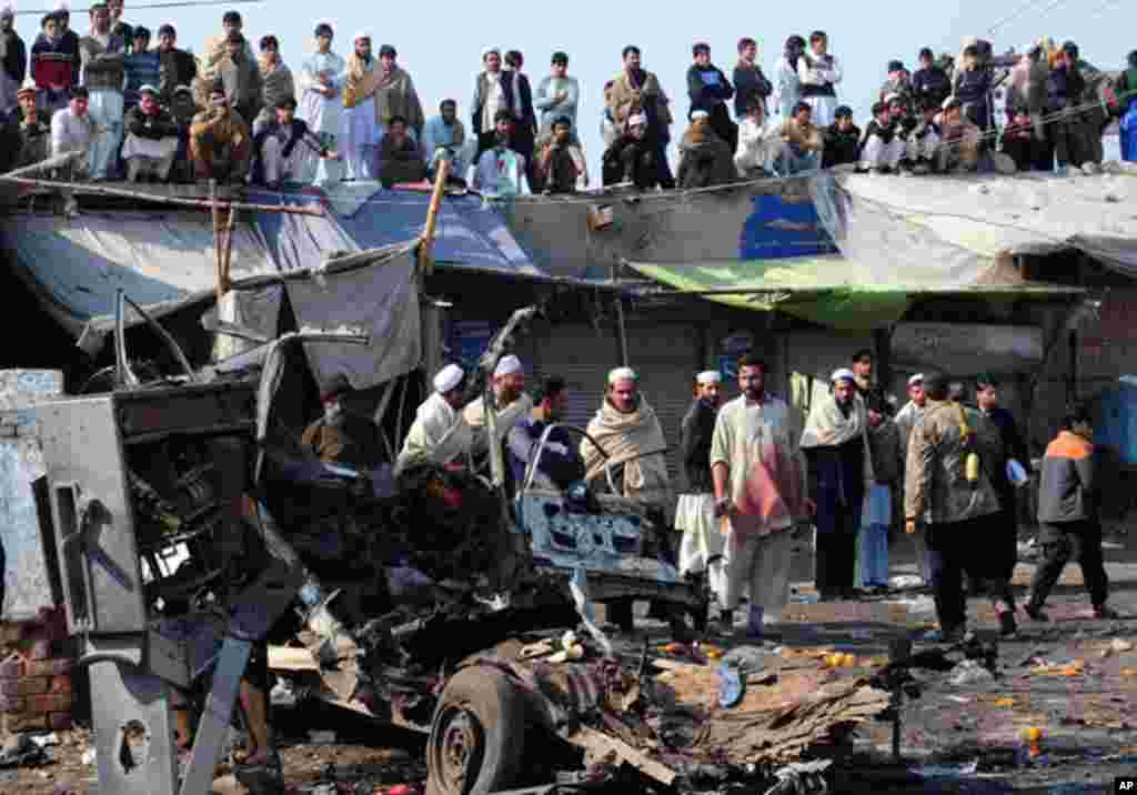 Pakistani local residents gather at the site of a bomb blast in Jamrud, January 10, 2012. (AFP)