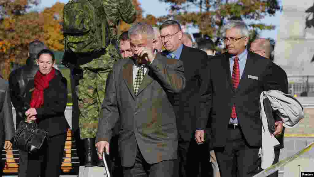 A man wipes a tear from his eye after paying his respects at the National War Memorial in downtown Ottawa, Oct. 23, 2014.