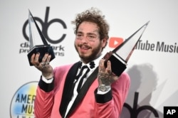 "Post Malone poses in the press room with the awards for favorite male pop/rock artist and favorite rap/hiphop album for ""Beerbongs & Bentleys"" at the American Music Awards, Oct. 9, 2018, in Los Angeles."