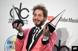 """Post Malone posa en la sala de prensa con los premios a su artista favorito de pop / rock masculino y su álbum favorito de rap / hiphop por """"Beerbongs & Bentleys"""" en los American Music Awards, octubre 9, 2018, en Los Ángeles."""