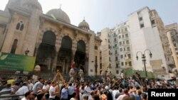 Pemrotes anti-Morsi dan polisi anti huru-hara berkumpul di luar masjid al-Fatah di Lapangan Ramses, Kairo (17/8).