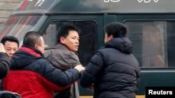 Ông Trương Tuyết Trung, luật sư của ông Triệu Thường Thanh từ chối đưa giấy tờ chứng minh cho cảnh sát mặc thường phục khi ông bị họ chận lại trên đường đến tòa án để dự phiên tòa xử ông Triệu ở Bắc Kinh, 23/1/14