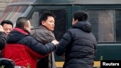Zhang Xuezhong (C), a lawyer for Chinese dissident Zhao Changqing, argues with plain-clothed policemen as he refuses to show them his identification card in Beijing, Jan. 23, 2014.