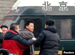 FILE - Zhang Xuezhong (C), a lawyer for Chinese dissident Zhao Changqing, argues with plain-clothed policemen as he refuses to show them his identification card when he was stopped and questioned by them on his way to court to attend Zhao's trial in Beijing January 23, 2014.