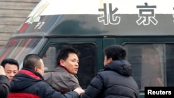 Zhang Xuezhong (C), a lawyer for Chinese dissident Zhao Changqing, argues with plain-clothed policemen as he refuses to show them his identification card when he was stopped and questioned by them on his way to court to attend Zhao's trial in Beijing, Jan. 23, 2014.