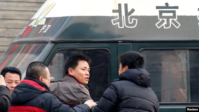 异议人士赵常青的律师张雪忠(中)在北京与便衣安全人员争论。(2014年1月23日)