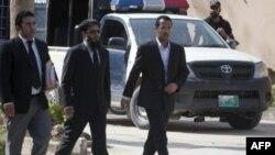 ذکریا احمد الفتاح، برادر جوانترین زن اسامه بن لادن همراه با امیر خلیل، یکی از وکلای خانواده بن لادن عازم جلسه دادگاه در محل نگهداری آنان هستند. دوم آوریل 2012