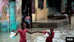 2 anak berjalan dalam air akibat banjir di Haiti, di khawatirkan penyakit Kolera yang menyebar ke luar daerah Artibonite berasal dari air.