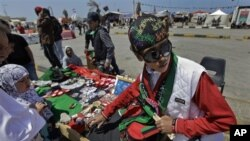A youth sells hats, flags, and other souvenirs in the colors of the opposition flag to those gathering for Friday prayers in the square next to the courthouse on the corniche in Benghazi, Libya April 15, 2011