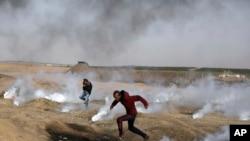 巴勒斯坦抗议者在加沙地带和以色列边界地区躲避以军发射的催泪瓦斯。(2018年4月13日)