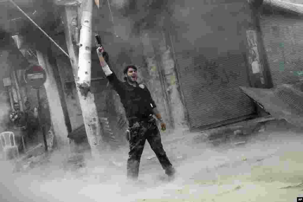 Un rebelde hace un llamado a la victoria ante el asedio de las tropas gubernamentales.