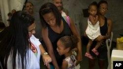 Tais da Silva Almeida tranquiliza a su hija de cinco años, mientras una trabajadora de salud se prepara para vacunarla contra la fiebre amarilla. Brasil, Marzo 17, 2017.