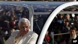 Pope Benedict XVI waves as he is driven through the crowd in St. Peter's Square during a pep rally for Catholic youths, at the Vatican, 30 Oct 2010