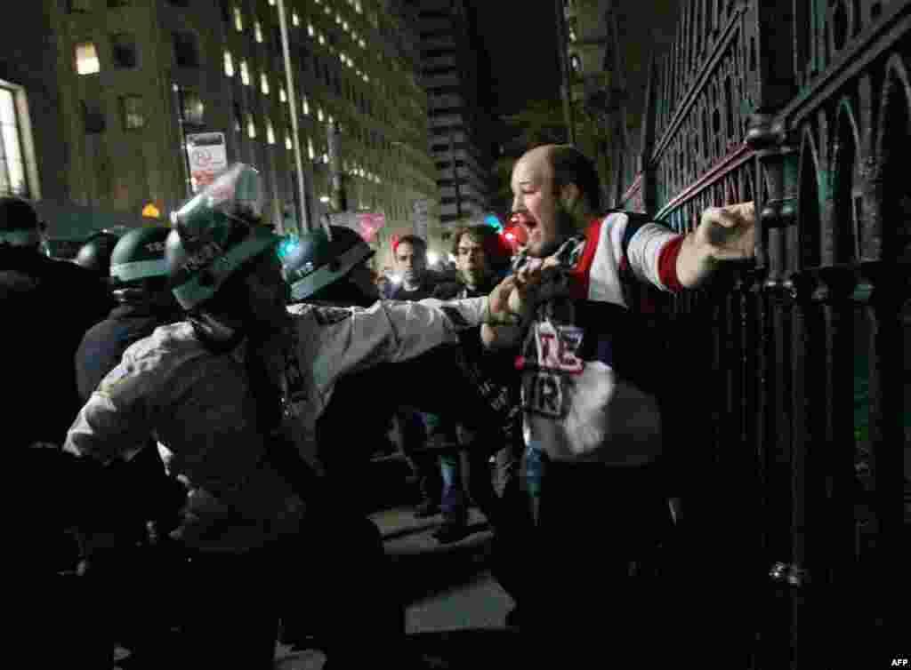 15 tháng 11: Một người biểu tình thuộc phong trào Chiếm Lĩnh Wall Street bị cảnh sát bắt trong khi cắm trại ở công viên Zuccotti, gần thị trường chứng khoán New York. Cảnh sát nói cần giải tán cuộc cắm trại vì vấn đề vệ sinh. (AP Photo/Mary Altaffer)