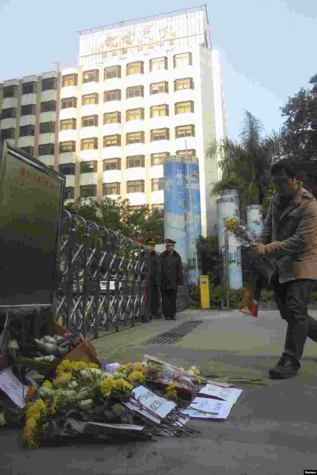 A man lays a bouquet of chrysanthemums in front of the headquarters of Southern Weekly newspaper, January 7, 2013.