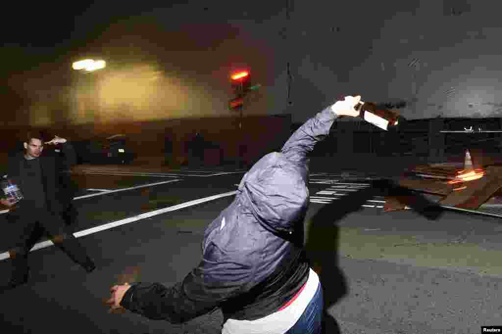 A protester throws a bottle at police officers following the election of Republican Donald Trump as President of the United States in Oakland, California, U.S., Nov. 9, 2016.