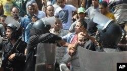Pasukan keamanan Mesir mengawal seorang pendukung Ikhwanul Muslimin keluar dari Masjid al-Fatah (17/8).