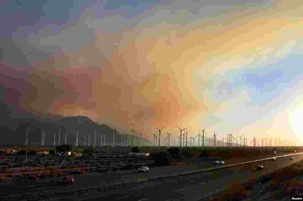 Smoke rises above wind turbines near Interstate 10 in Banning, California August 8, 2013. The wildfire has forced the evacuation of 500 homes in several small communities east of Los Angeles.