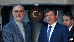 Menlu Iran Ali Akbar Salehi (kiri) dan Menlu Turki Ahmet Davutoglu sesaat sebelum pembicaraan terkait krisis Suriah di Ankara, Turki (7/8).