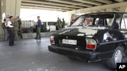 View of broken glass from a damaged police car at the site of a bomb blast in central Damascus April 27, 2012.