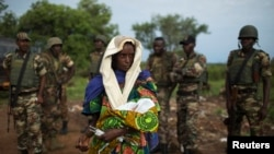 FILE - The relative of a woman that recently gave birth yesterday to twins holds one of the babies before departing towards Chad's border, escorted by troops from the African Union operation in CAR (MISCA) in the northern town of Kaga Bandoro.