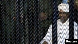 Sudan's former president Omar Hassan al-Bashir sits guarded inside a cage at the courthouse where he is facing corruption charges, in Khartoum, Sudan August 19, 2019.
