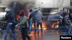Manifestantes lanzan piedras y cocteles molotov contra la policía durante protestas en Kiev.