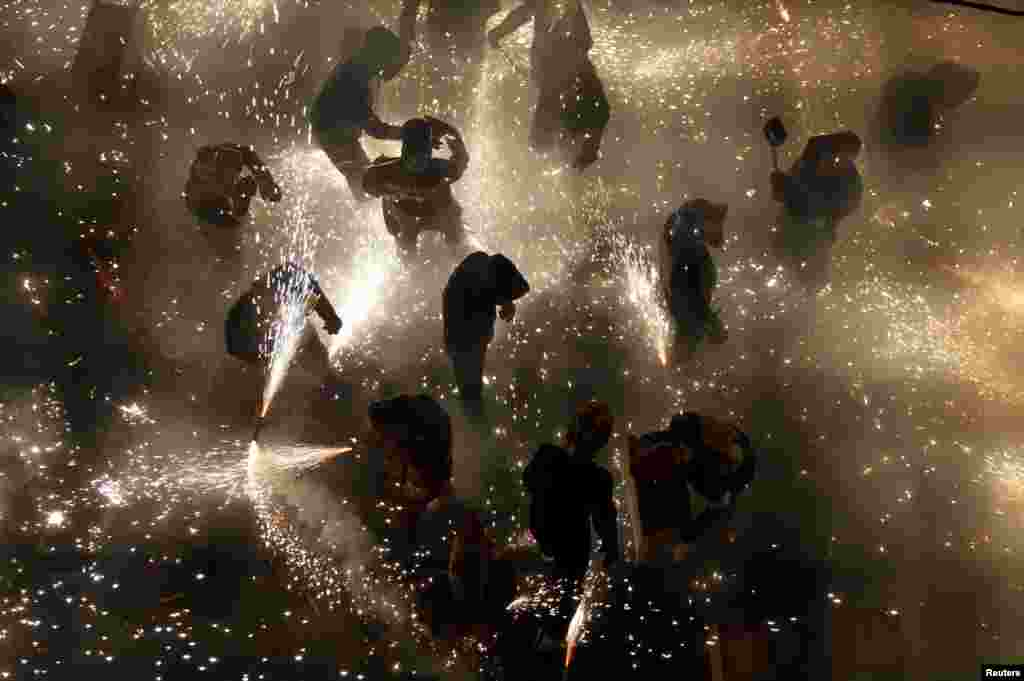 """Revelers play with fireworks in an enclosed area on the main street of the village of Paterna, near Valencia, during the annual """"Corda"""" festivity in Spain, Aug. 26, 2013."""