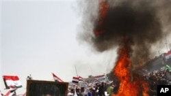Followers of radical Shi'ite cleric Moqtada al-Sadr, seen in the poster, burn US flags during a rally marking the eighth anniversary of the fall of the Iraqi capital to American troops in Baghdad, Iraq, April 9, 2011
