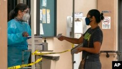 FILE - A patient shows her COVID-19 vaccination card at the Clínica Monseñor Oscar A. Romero in the Pico-Union district of Los Angeles, July 26, 2021.