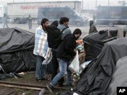 Những người di dân cố vơ vét lại đồ đạc trước khi bị nhà chức trách Pháp đuổi khỏi những khu ở tạm, nơi tập trung nhiều di dân từ Trung Đông, châu Phi, và châu Á