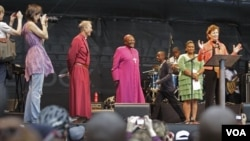 South African Archbishop Desmond Tutu, center, listens as former Irish President Mary Robinson speaks during a climate justice rally in Durban, South Africa, Sunday, Nov. 27, 2011. Amid fresh warnings of climate-related disasters in the future, delegates