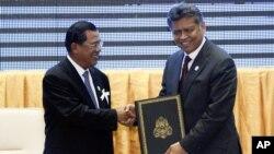 Thủ tướng Campuchia Hun Sen và Tổng Thư ký ASEAN Surin Pitsuwan bắt tay sau buổi lễ thông qua Tuyên bố ASEAN về Nhân quyền tại Phnom Penh, ngày 18/11/2012.