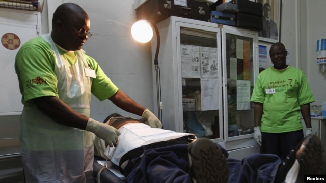 FILE - A doctor (L) performs circumcision on an unidentified politician in an effort to reduce the spread of HIV, in Harare, Zimbabwe, June 22, 2012.