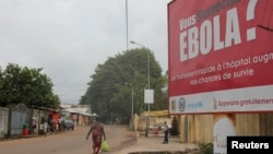 FILE - A billboard with a message about Ebola appears on a street in Conakry, Guinea, Oct. 26, 2014.